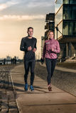 Active young couple jogging on a harbor promenade Stock Photo