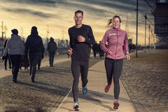 Active young couple jogging on a harbor promenade Stock Photos