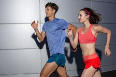 Active young couple jogging side by side in an urban street during their daily workout in a health and fitness concept royalty free stock photography