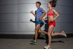 Active young couple jogging side by side in an urban street during their daily workout in a health and fitness concept royalty free stock image