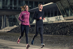 Active young couple jogging in an urban street. Active young couple jogging side by side in an urban street during their daily workout in a health and fitness royalty free stock image