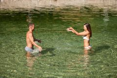 Active young couple plays in shallow water on a hot summer morning.  stock photo