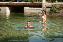Active young couple plays in shallow water on a hot summer morning.  royalty free stock image