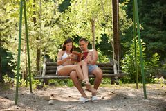 Active young couple reading tourist guide book on a swing in par Stock Photos