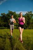 Active young couple running in the park.  Royalty Free Stock Images