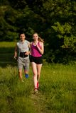 Active young couple running in the park. In summer Royalty Free Stock Image