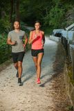 Active young couple running in park. An evening workout Stock Image