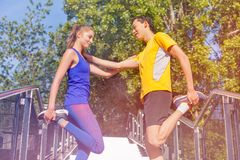 Active young couple stretching legs outdoors. Active young couple stretching legs standing at the city stairs opposite to each other at sunny day Royalty Free Stock Photo