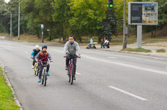 Active young father with son and daughter having bicycle ride on a Dnepr river embankment. DNEPR, UKRAINE - SEPTEMBER 25, 2016:Active young father with son and royalty free stock photos