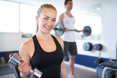 Active Young Female Lifting Dumbbell in the Gym. Close up Pretty Active Young Female Lifting Dumbbell in the Gym and Smiling at the Camera Royalty Free Stock Images