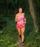 Active young fit woman runs in green forest on late summer after Stock Photos