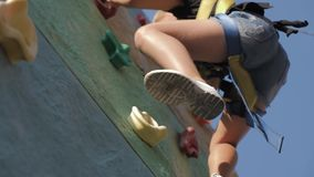 Active young girl on adventure park, training climbing. Child to pass difficult section of an obstacle course. Active