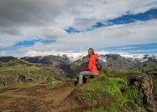 Active young hiker woman small backpack sitting enjoying volcano landscape with glacier mountains green valley and snow Thorsmork royalty free stock photo