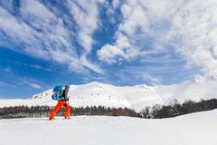 Active young man backcountry skiing on a beautiful sunny day, wi. Active man backcountry skiing on a beautiful sunny day, with high mountains covered with snow Royalty Free Stock Image