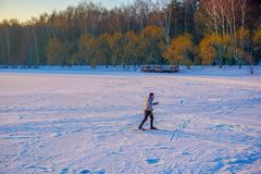 Active young man cross-country skiing on huge frozen lake during lovely winter sunset stock photo