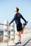 Active young man standing on one legs. Portrait of active young man standing on one legs stretching exercise Stock Photos
