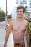 An active young man with a surfboard Stock Image