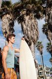 An active young man with a surfboard Stock Photos