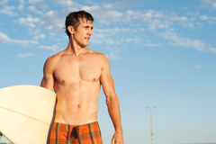 An active young man with a surfboard at the beach Royalty Free Stock Photos