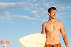 An active young man with a surfboard at the beach Stock Photography