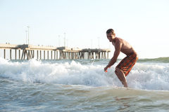 Active young man surfing in the ocean Royalty Free Stock Images