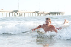 Active young man surfing in the ocean Stock Photos