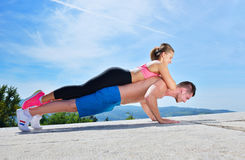 Active young man and woman exercising doing push ups. royalty free stock image