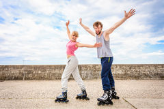 Active young people friends rollerskating outdoor. Stock Images