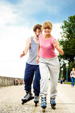 Active young people friends rollerskating outdoor. Royalty Free Stock Photo