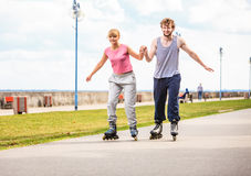 Active young people friends rollerskating outdoor. Royalty Free Stock Photos