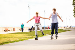 Active young people friends rollerskating outdoor. Royalty Free Stock Photography