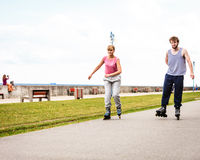 Active young people friends rollerskating outdoor. Royalty Free Stock Image