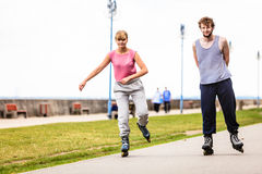 Active young people friends rollerskating outdoor. Royalty Free Stock Images