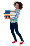 Active young school kid carrying books stock images