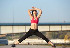 Active young sports woman  stretching body muscles Royalty Free Stock Photography