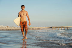 Active young surfer holding a surfboard. At the beach Royalty Free Stock Photo