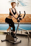 Active young woman doing exercise on bicycle at home Stock Photos
