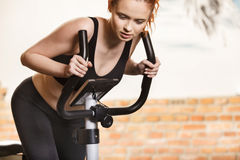 Active young woman doing exercise on bicycle at home Stock Photo