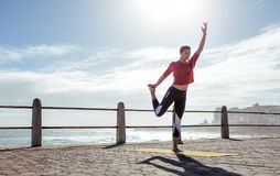 Active young woman doing yoga exercises. Active young woman doing stretching exercises outdoors. Fitness woman exercising in yoga pose on the road by the sea Royalty Free Stock Photography
