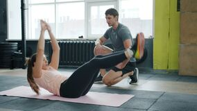 Active young woman exercising abdominal muscles training with trainer in gym