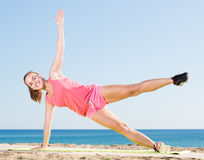 Active young woman exercising on exercise mat outdoor. At the seaside Royalty Free Stock Photo