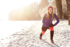 Active young woman exercising in snow Royalty Free Stock Photography