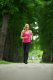 Active young woman jogging in the park Stock Images