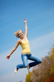 Active young woman jumping high in sunshine Royalty Free Stock Photography