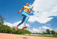 Active young woman jumping at stadium in summer Royalty Free Stock Image
