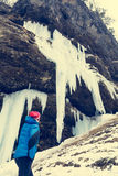 Active young woman looking at frozen icicles. Exploring Pericnik waterfall in Vrata valley, Slovenia Royalty Free Stock Image