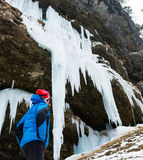 Active young woman looking at frozen icicles. Exploring Pericnik waterfall in Vrata valley, Slovenia Stock Photo