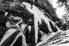 Active young woman looking at frozen icicles. Exploring Pericnik waterfall in Vrata valley, Slovenia Royalty Free Stock Images