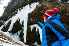 Active young woman looking at frozen icicles. Stock Photo