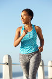 Active young woman running and listening to music with earphones Royalty Free Stock Image
